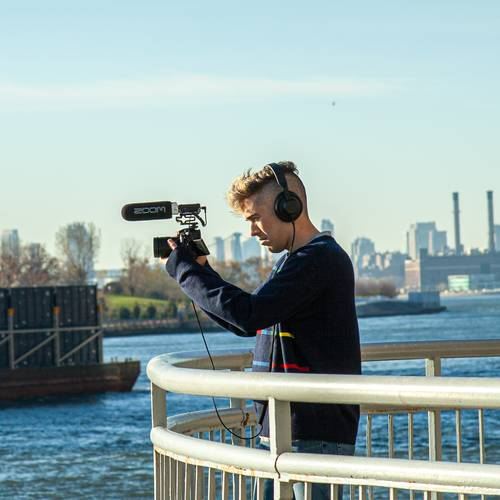 videographer recording with F1-SP mounted on a DSLR camera under the 59th Street bridge, New York City