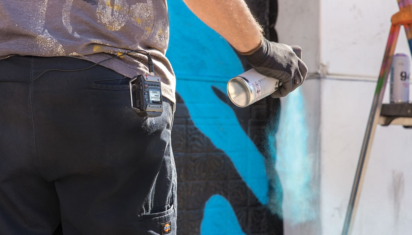 Street artist using spray paint to create his artwork, with F1 connected to his belt
