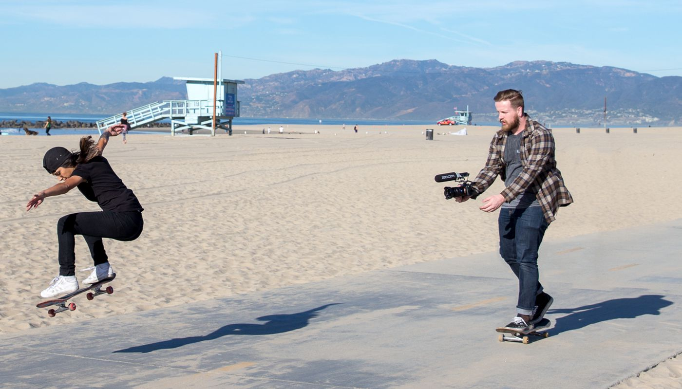 Videographer with F1-SP mounted to a DSLR on a skateboard, filming another skateboarder performing a trick