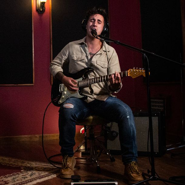 Aaron Rizzo Sitting singing with guitar