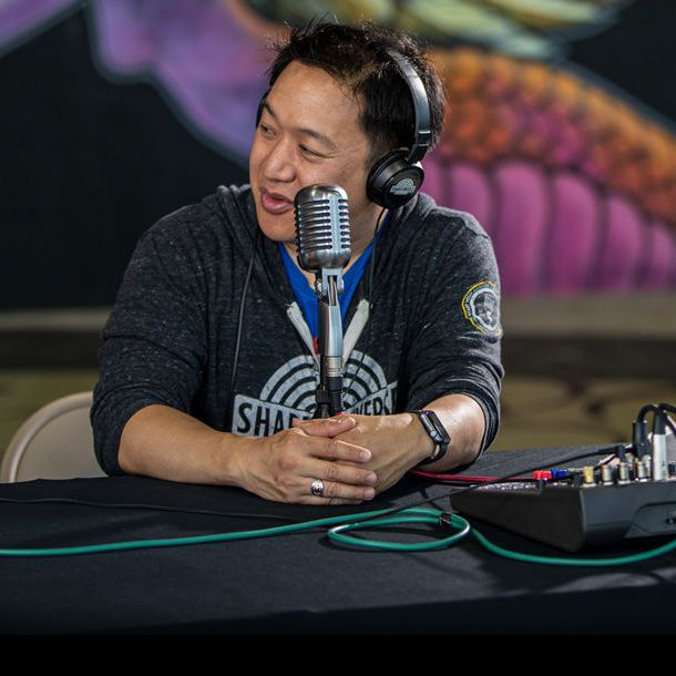 Ming Chen sitting with microphone recording a podcast