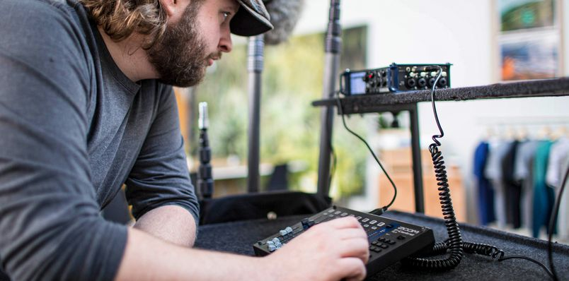 Location sound engineer using faders on F-Control to fine-tune recording on the F8n.