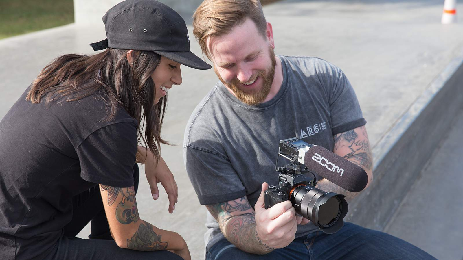 Videographer and skateboarder reviewing footage on DSLR camera with F1-SP mounted