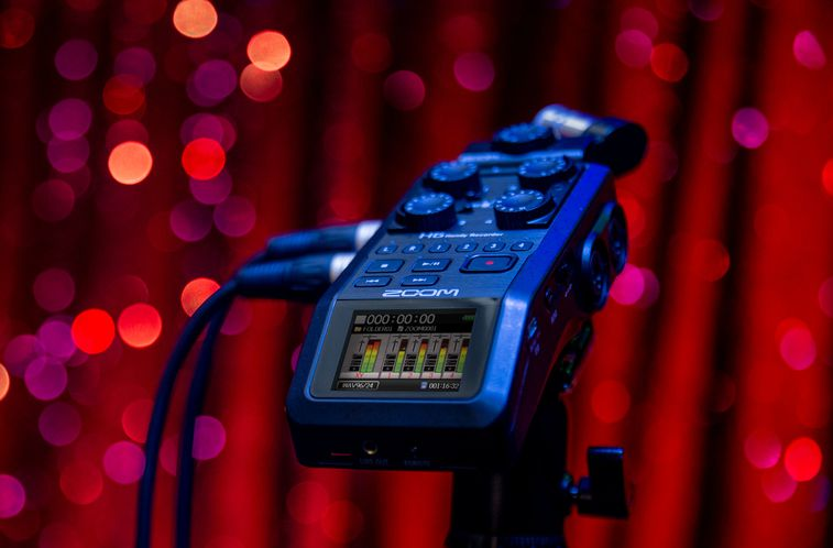 H6 on stage with red sparkle curtains
