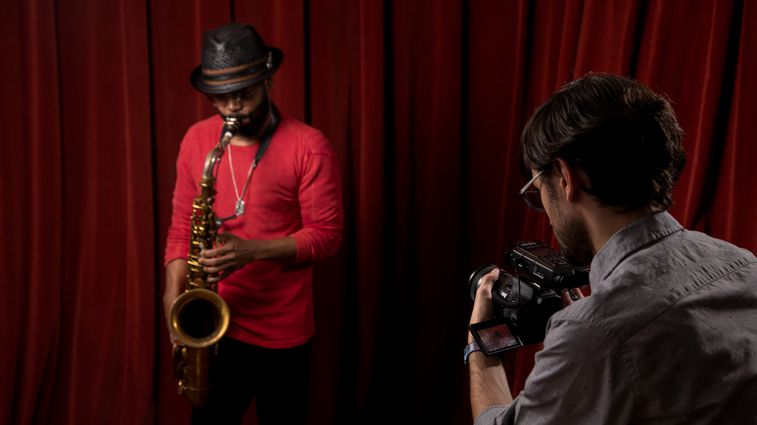 Saxaphonist Mark Shim plays while a videographer records him using a DSLR camera with an H4n Pro mounted to it, recording audio.