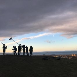 A silhouetted production crew using Zoom equipment to capture audio atop a hill overlooking a coastal village.