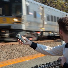 A creator using a Zoom H1N to capture audio from a nearby train passing by.